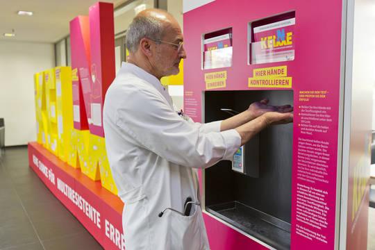 """Mann desinfiziert seine Hände, daneben die Ausstellung der Kampagne """"Keine Keime""""."""