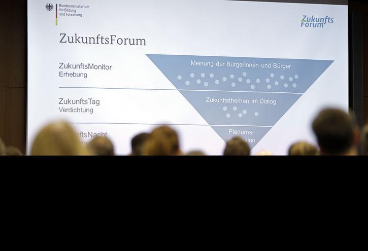 Besucherinnen und Besucher betrachten den Ablauf des ZukunftsForums III.